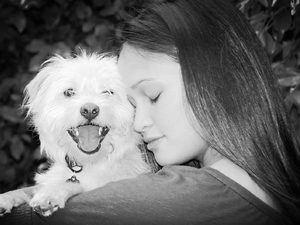 woman cuddling happy smiling terrier dog